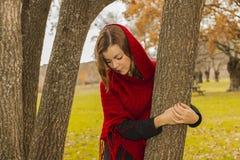Женщина нося красную плащпалату шерстей смотря вниз с обнимать дерево Стоковые Фотографии RF