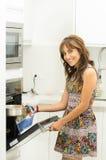 Женщина нося красочное платье в современной двери печи отверстия кухни держа mittens и варя бак металла усмехаясь к Стоковое Изображение