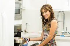 Женщина нося красочное платье в современной кухне Стоковые Изображения