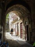 Женщина нося пакеты гуляет вверх по крутой улице Лиссабону Португалии булыжника Стоковые Изображения