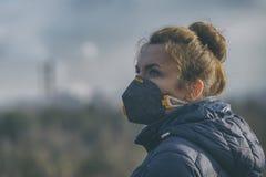Женщина нося реальный лицевой щиток гермошлема анти--загрязнения, анти--смога и вирусов стоковое фото rf