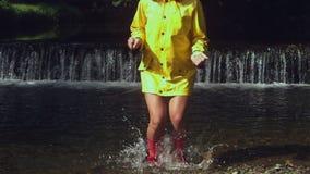 Женщина нося розовые резиновые ботинки брызгая в воде сток-видео