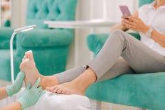 Женщина нося серые брюки сидя наслаждающся массажем ног стоковое изображение