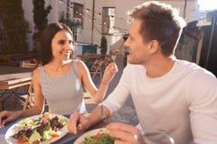 Женщина нося туго striped платье имея ужин с ее человеком стоковое фото