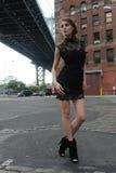 Женщина нося черный minidress стоя под мостом Манхаттана стоковое изображение rf