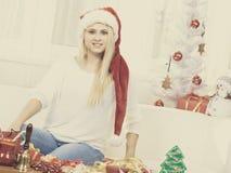 Женщина нося шляпу santa ослабляя на софе Стоковое Изображение