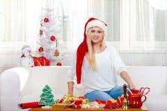 Женщина нося шляпу santa ослабляя на софе Стоковые Фото