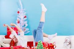 Женщина нося шляпу santa ослабляя на софе Стоковое Фото