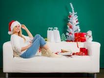 Женщина нося шляпу santa ослабляя на софе Стоковая Фотография