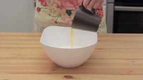 Женщина добавляет топлёное масло в белом шаре акции видеоматериалы