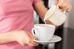 Женщина добавляя молоко к ее кофе стоковые фото
