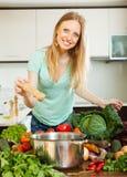 Женщина добавляя специи или соль к баку стоковое фото rf