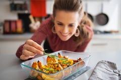 Женщина добавляя rosmarinus к испеченной тыкве closeup стоковые фото