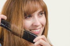 Женщина обматывает волосы завивая утюга Стоковое Изображение