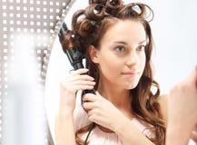 Женщина обматывает волосы на роликах Стоковые Изображения