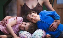 Женщина обнимая детей на террасе деревянного дома стоковая фотография