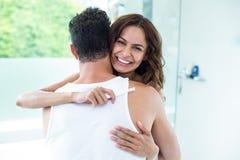 Женщина обнимая супруга пока держащ набор беременности стоковые фото