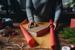 Женщина оборачивая книгу как подарок рождества Стоковая Фотография