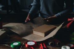 Женщина оборачивая книгу как подарок рождества Стоковое Фото
