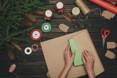 Женщина оборачивая подарок рождества Стоковая Фотография