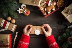 Женщина оборачивая современные подарки на рождество с пустой биркой подарка на старой деревянной предпосылке Взгляд птицы глаза Стоковое фото RF
