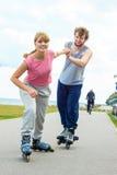 Женщина ободряет человека сделать rollerblading Стоковая Фотография