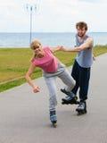 Женщина ободряет человека сделать rollerblading Стоковое Изображение