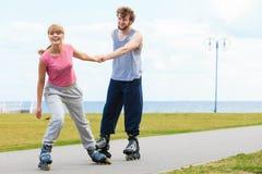 Женщина ободряет человека сделать rollerblading Стоковая Фотография RF