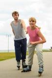 Женщина ободряет человека сделать rollerblading Стоковое Изображение RF