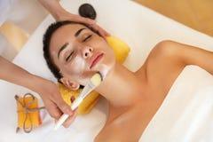 женщина обработки лицевого щитка гермошлема огурца белая Женщина в салоне красоты получает морскую маску стоковое фото rf