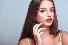 женщина обработки лицевого щитка гермошлема огурца белая Женщина при здоровая сторона прикладывая косметическую сливк стоковое фото rf