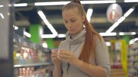 Женщина образа жизни выбирает йогурт в супермаркете сток-видео