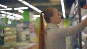 Женщина образа жизни выбирает молочные продучты в супермаркете видеоматериал