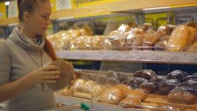 Женщина образа жизни выбирает хлеб в супермаркете сток-видео