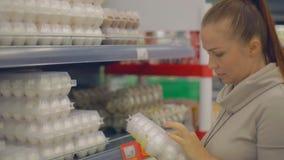 Женщина образа жизни выбирает яйца в супермаркете видеоматериал