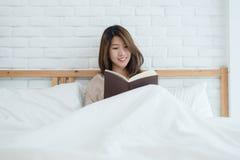 Женщина образа жизни счастливая молодая азиатская наслаждаясь лежать на удовольствии книги чтения кровати в вскользь одежде дома Стоковая Фотография RF