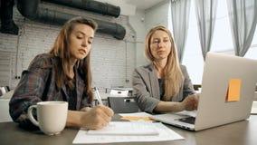 Женщина 2 обсуждая проект бизнес-плана и запуска сток-видео