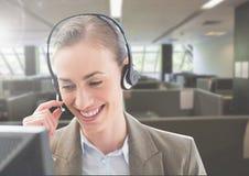 Женщина обслуживания клиента говоря на наушниках в офисе стоковое фото rf