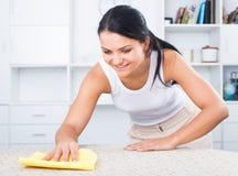 Женщина обтирает мебель от пыли Стоковое Изображение RF