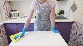 Женщина обтирает таблицу в кухне акции видеоматериалы