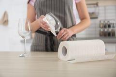 Женщина обтирая бокал с бумажным полотенцем в кухне стоковое изображение rf