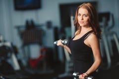 Женщина общается с гантелями в спортзале Стоковая Фотография RF
