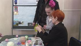 Женщина объясняет маленькую девочку с цветком на голове как вяжущ вязанием крючком празднество творение handmade видеоматериал