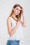 Женщина довольно молодой сексуальной моды чувственная представляя на белой предпосылке стены одетой в обмундировании джинсов стил Стоковые Изображения RF