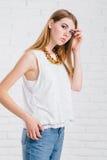 Женщина довольно молодой сексуальной моды чувственная представляя на белой предпосылке стены одетой в обмундировании джинсов стил Стоковые Фотографии RF