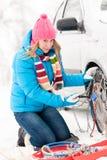 Женщина одевая в цепи автошины зимы автомобиля Стоковые Изображения RF