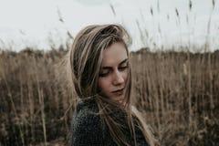 Женщина одела в пальто шерстей рассматривая вниз ее плечо Bulrush предпосылки напольно Съемка средства стоковое фото rf