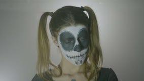 Женщина одетая как злая кукла репетируя страшные выражения стороны на хеллоуин показывает с составом краски стороны черепа - видеоматериал