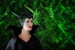 Женщина одетая как fairy ведьма в плаще и с рожками Стоковое Изображение