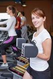 Женщина около подниматься crosstrainer Стоковое Изображение